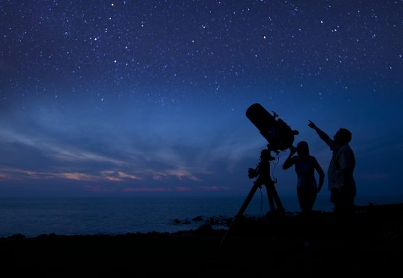 Astronomists study the stars during nightfall.