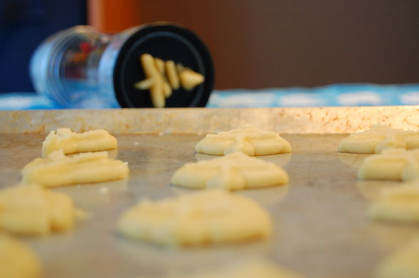 Spritz cookie dough on a cookie sheet with a Spritz press in the background