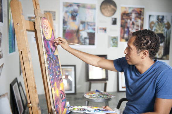 An artist working on a painting at the McColl Center for Visual Arts