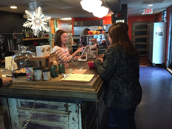 A clerk cheerfully rings up a customer at Smelly Cat.