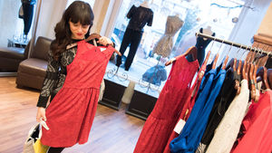 A young woman examines a dress in a Georgetown store